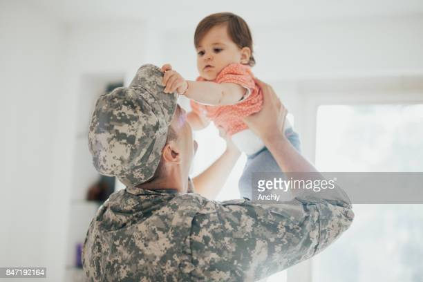 Baby girl trying to take off dad's military hat