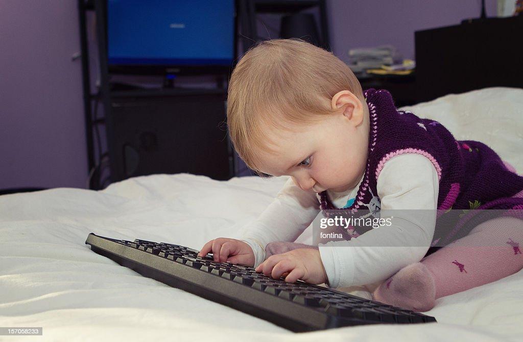 Baby girl typing on keyboard : Stock Photo