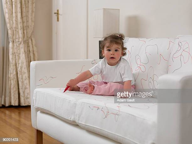 Baby girl using marker on sofa