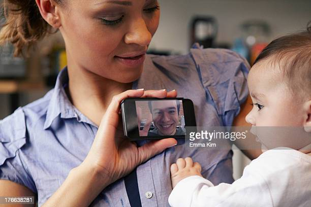 Baby girl watching father on video call, mother holding smartphone
