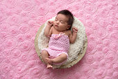 Portrait of a sleeping, one month old baby girl wearing a crocheted, pink romper.