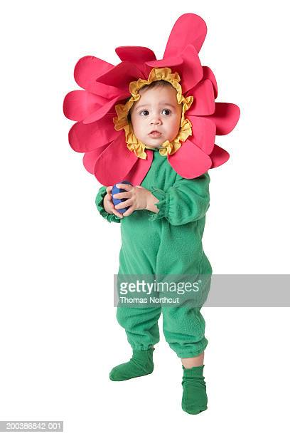Baby girl (12-15 months) wearing flower costume, looking away