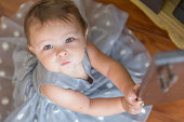 Baby girl wearing party dress, looking up