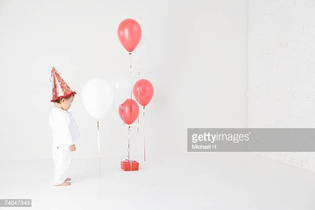 Baby girl (15-18 months) wearing party hat standing in studio, looking at balloons and present
