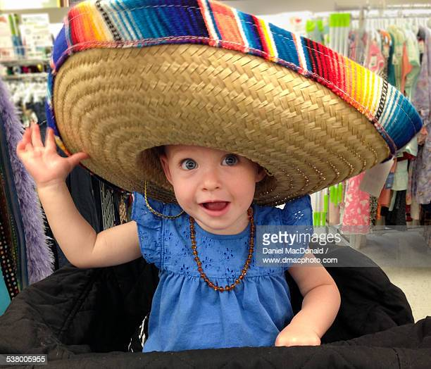 Baby girl wearing sombrero in thrift store