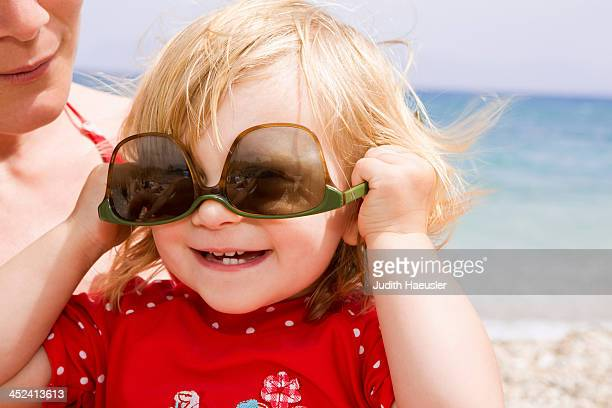 Baby girl wearing sunglasses upside down