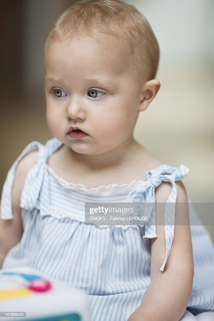 Baby girl with a musical block toy : Stock Photo