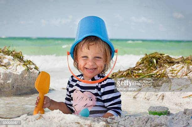 Baby girl with bucket over head on beach, Anna Maria Island, Florida, USA