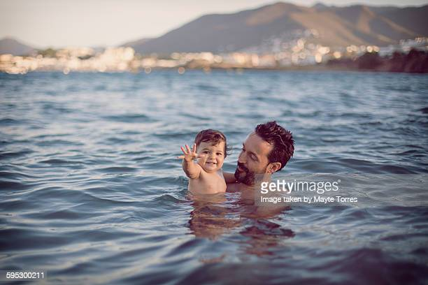 Baby girl with dad having a swim at the beach