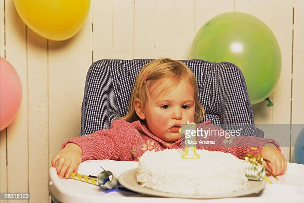 Baby girl with first birthday cake