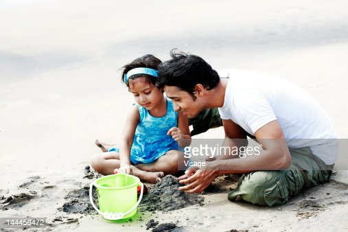 Baby girl with her father playing with sand at a beach : Stock Photo