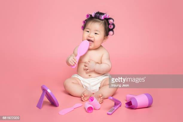 Baby girl (6-11 months) with her hair in curlers