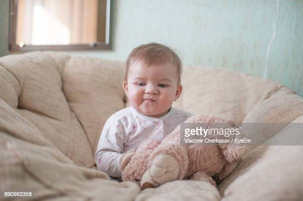 Baby Girl With Teddy Bear On Sofa At Home