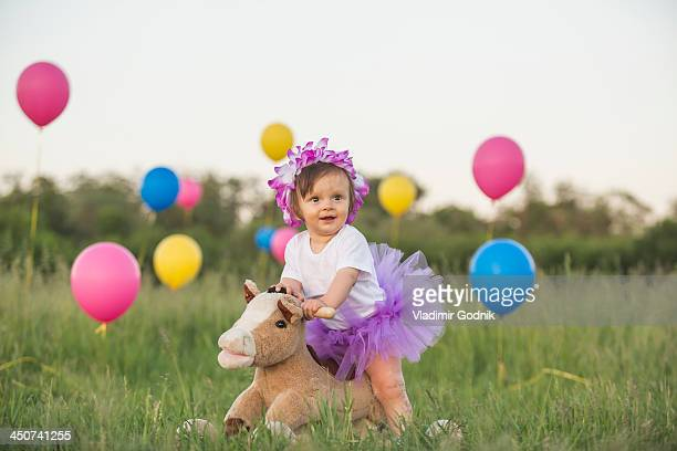 A baby girl with tutu on a rocking horse in a field with balloons