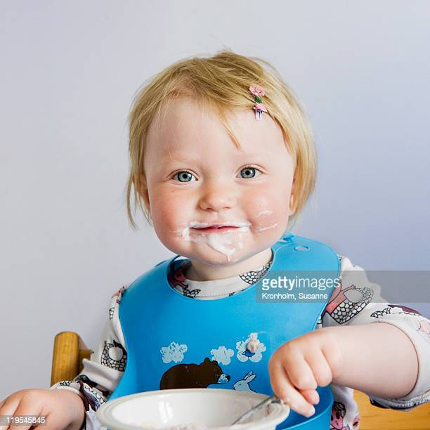 Baby girl with yoghurt on face, smiling