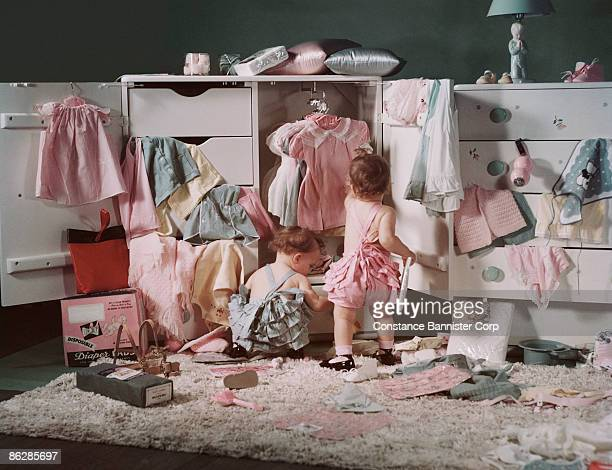Baby girls pulling clothes out of dresser