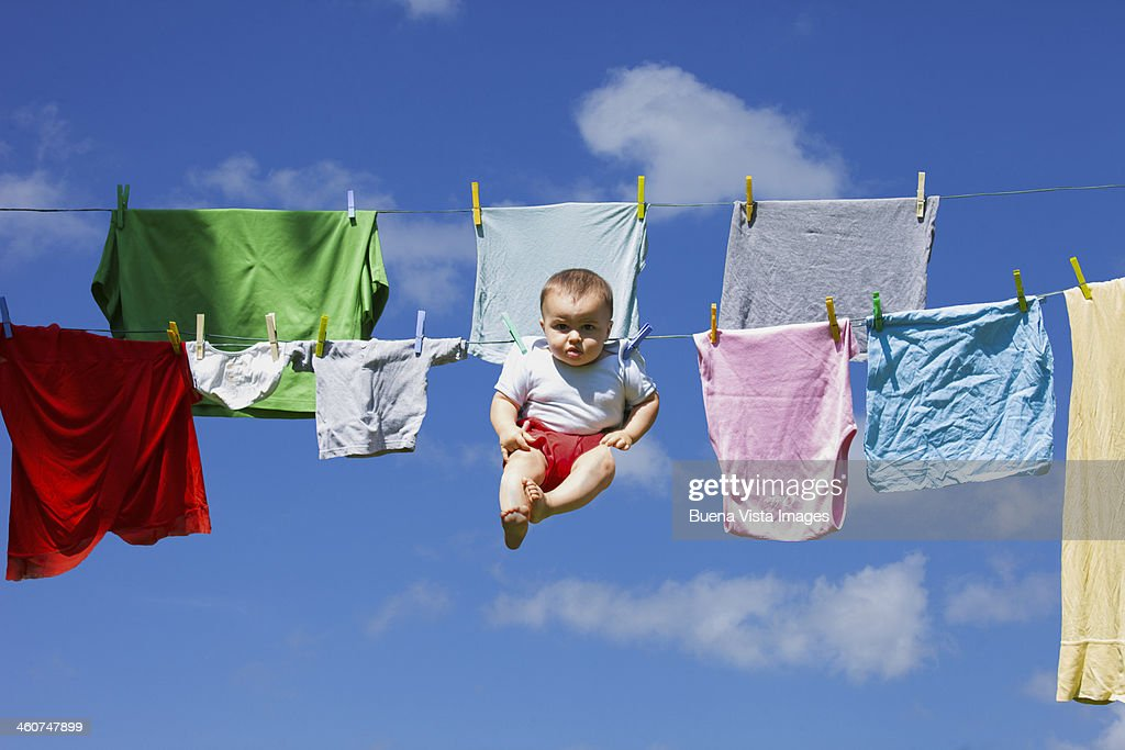 baby hanging to a drying clothing rope : Photo