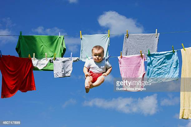 baby hanging to a drying clothing rope