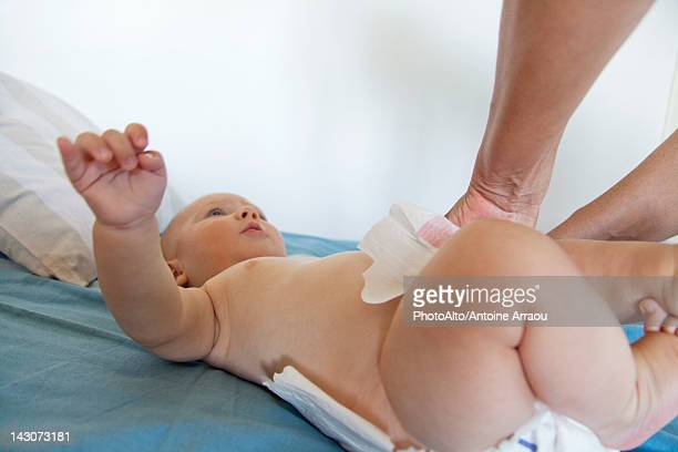 Baby having diaper changed, cropped