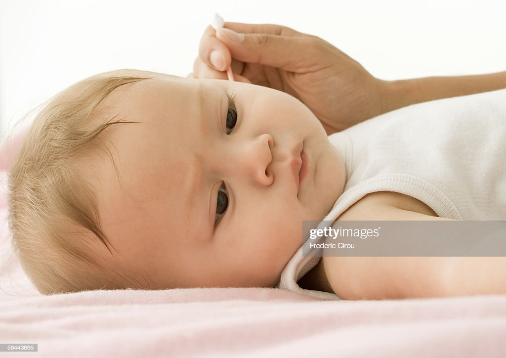 Baby having ear cleaned
