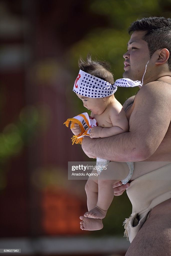 A baby, held by a sumo wrestler, is seen during the Nakizumo or crying baby sumo contest at Sensoji Temple on April 29, 2016 in Tokyo, Japan. Babies compete crying at this traditional festival which is believed to bring growth and good health to the infants.