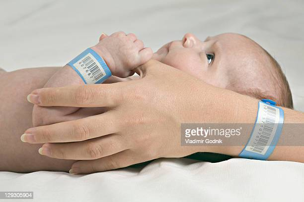 A baby holding her mother's thumb, both wearing hospital ID bracelets