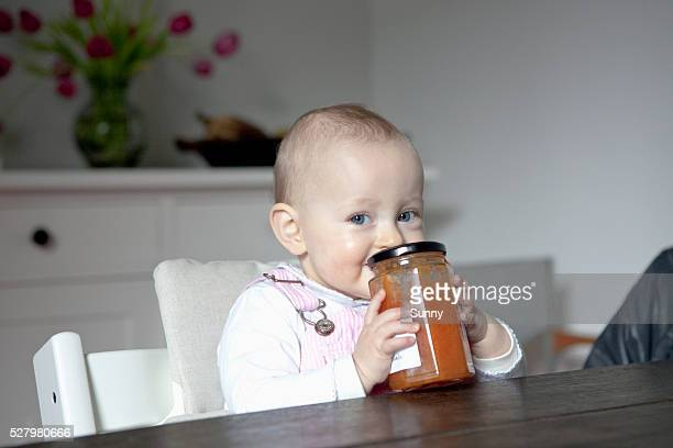 Baby holding jar of food