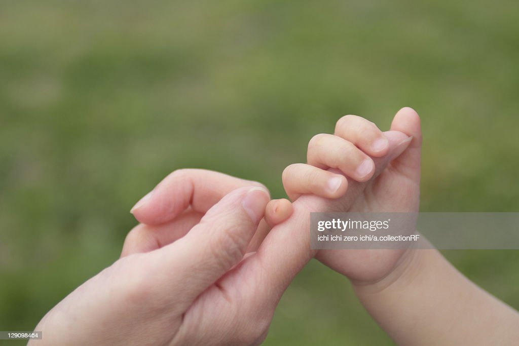 Baby holding Mother's finger : Stock Photo