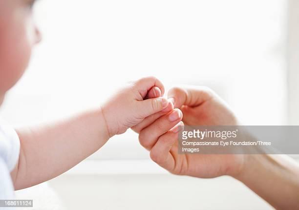 Baby holding mother's finger
