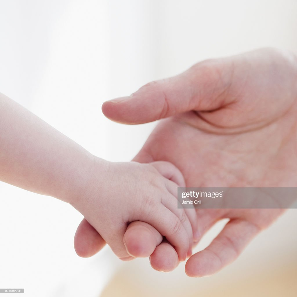 Baby holding mother's hand, close-up : Stock Photo