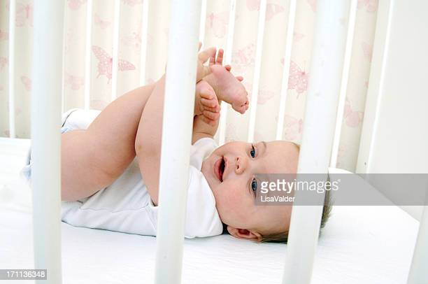 Baby holding their toes while lying in crib
