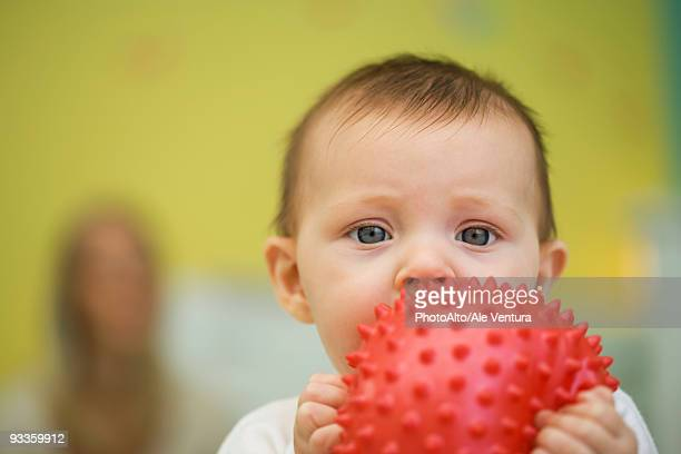 Baby holding toy in front of mouth