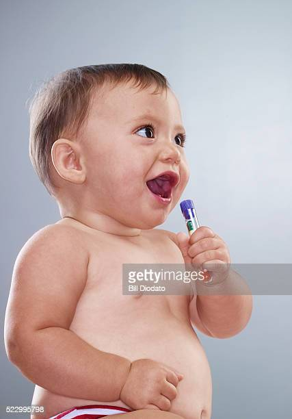 Baby Holding Vial of Drugs