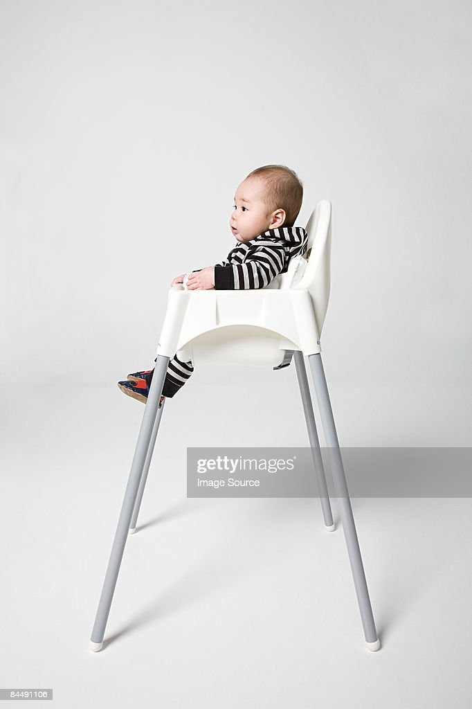 A baby in a high chair : Stock Photo