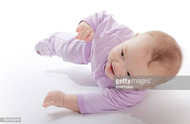 Baby in a purple jumper rolling around