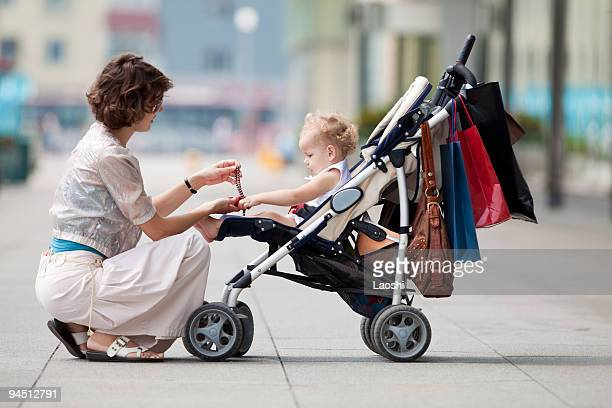 Baby in a stroller while her mother gives her a gift
