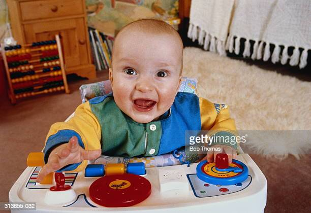 Baby (6-10 months) in baby walker with toys, smiling, close-up