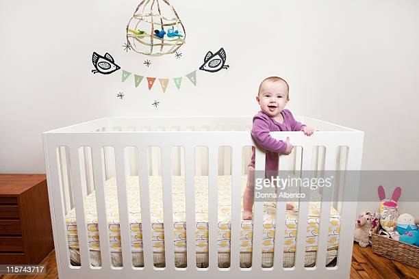 Baby in crib surrounded by toys