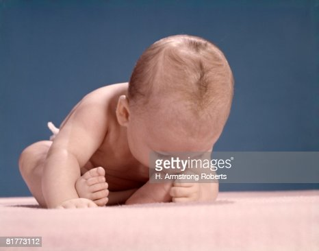 Baby In Diaper Falling Forward Mouth Biting Toes. : Stock Photo