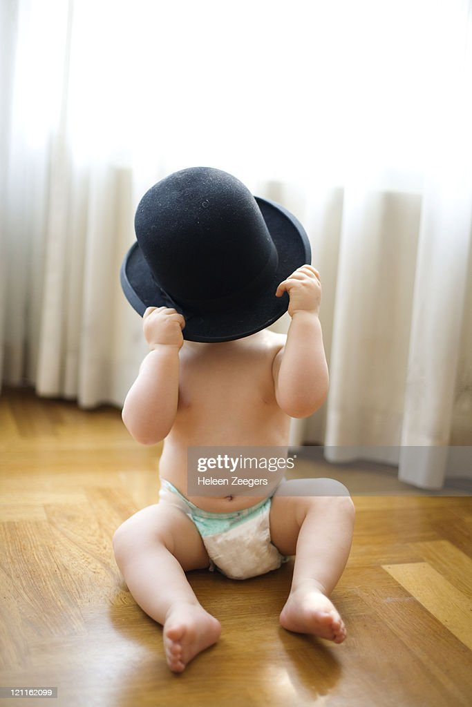 baby in diapers holding black hat in front of face : Stock Photo