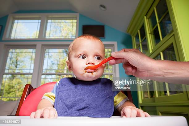 Baby In High Chair Eating Green Beans