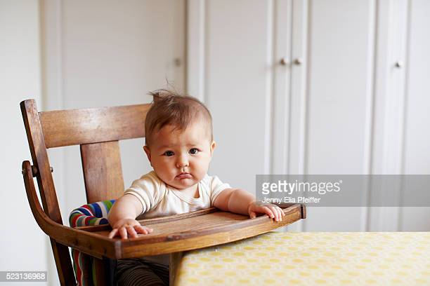 Baby (6-11 months) in high chair looking at camera
