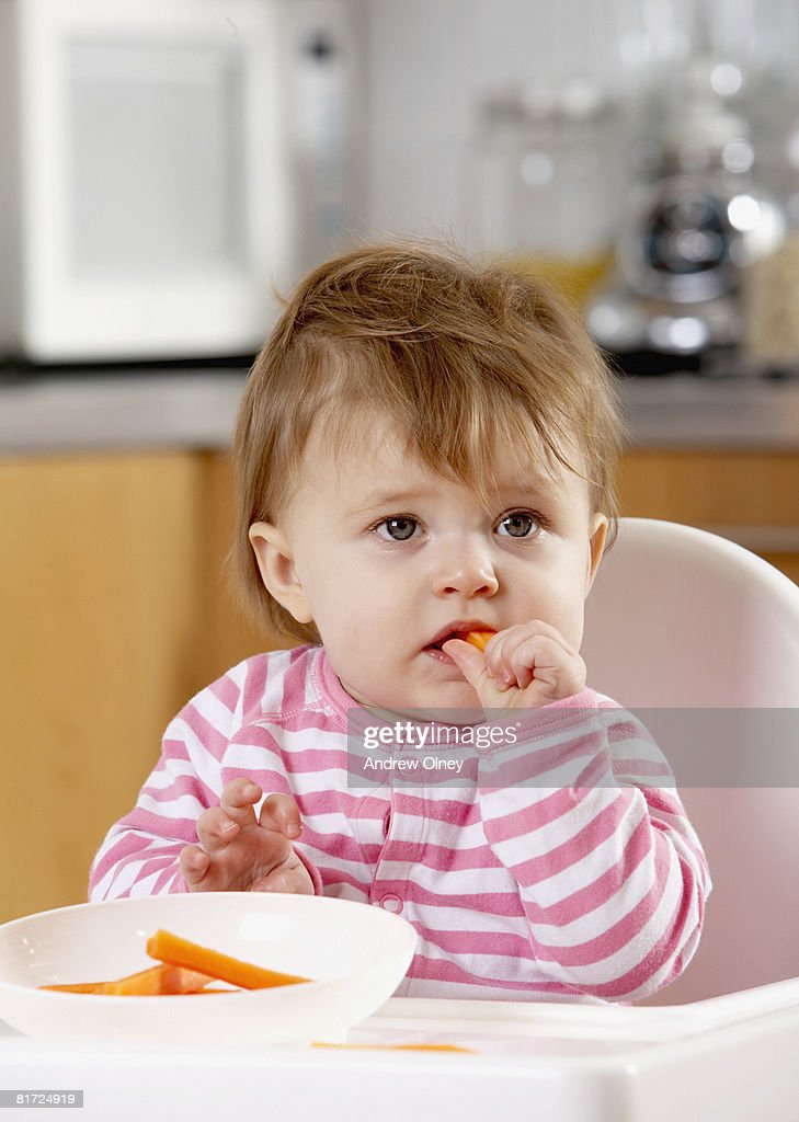 Baby in kitchen highchair eating carrot sticks : Stock Photo