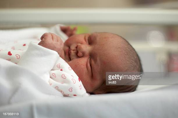 Baby in maternity ward cot