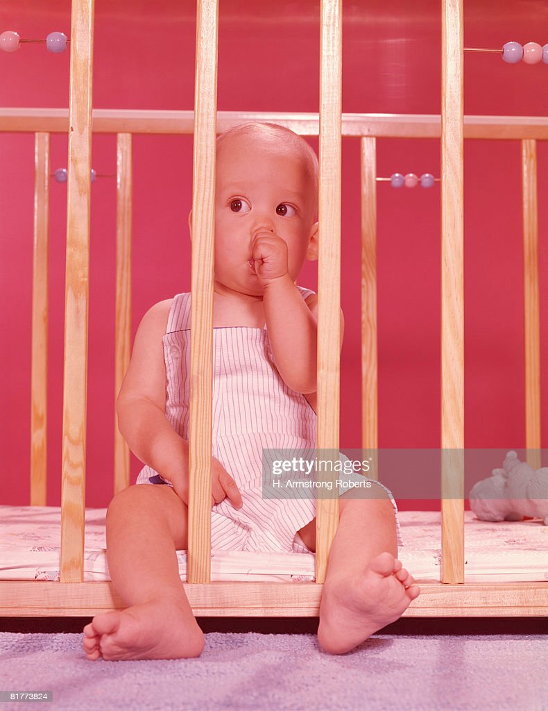 Baby in playpen, sucking thumb. (Photo by H. Armstrong Roberts/Retrofile/Getty Images) : Stock Photo