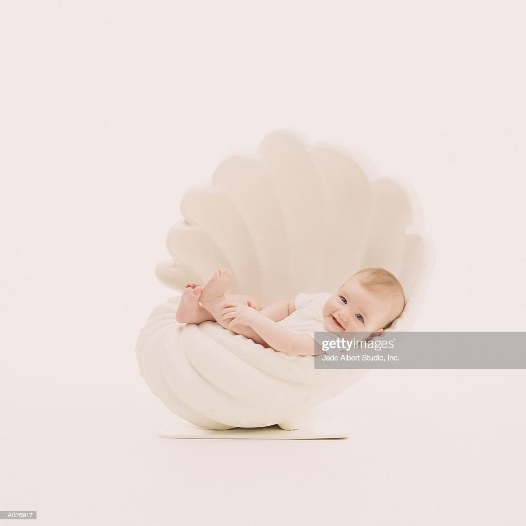 Baby (3-6 months) in shell shaped cradle : Stock Photo