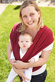 Baby In Sling With Mother Outdoors