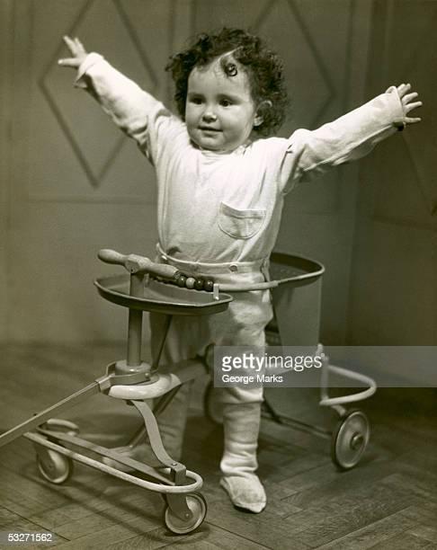 Baby in walker with hands up