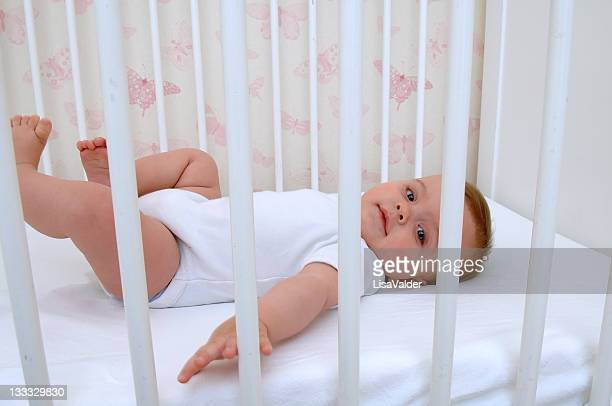 Baby in white lying on back in a white crib