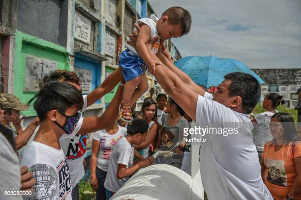 A baby is carried as a local tradition over the coffin of sixteen year old Arjay Suldao who was killed by unknown men after being missing for days...